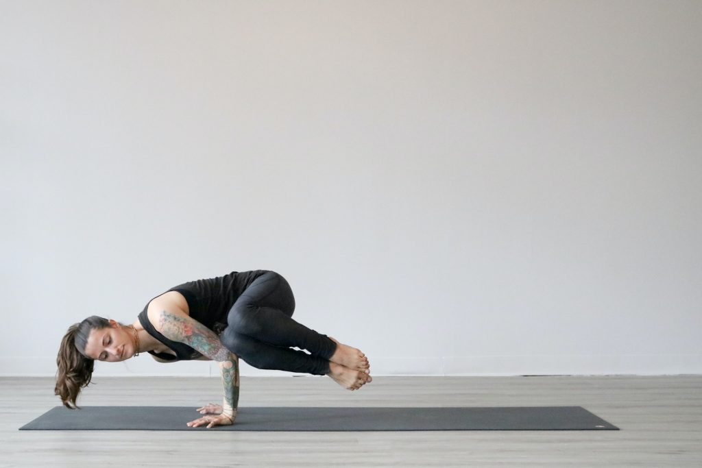 woman in black tank top and gray leggings doing yoga